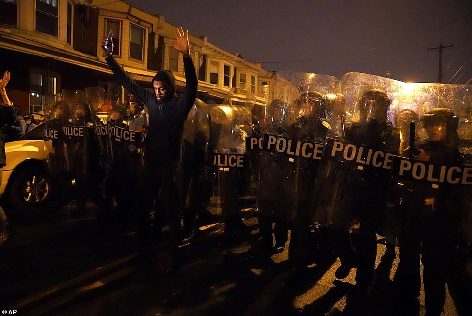 Sharif Proctor lifts his hands up in front of the police line during a protest in response to the police shooting of Walter Wallace Jr. on Monday