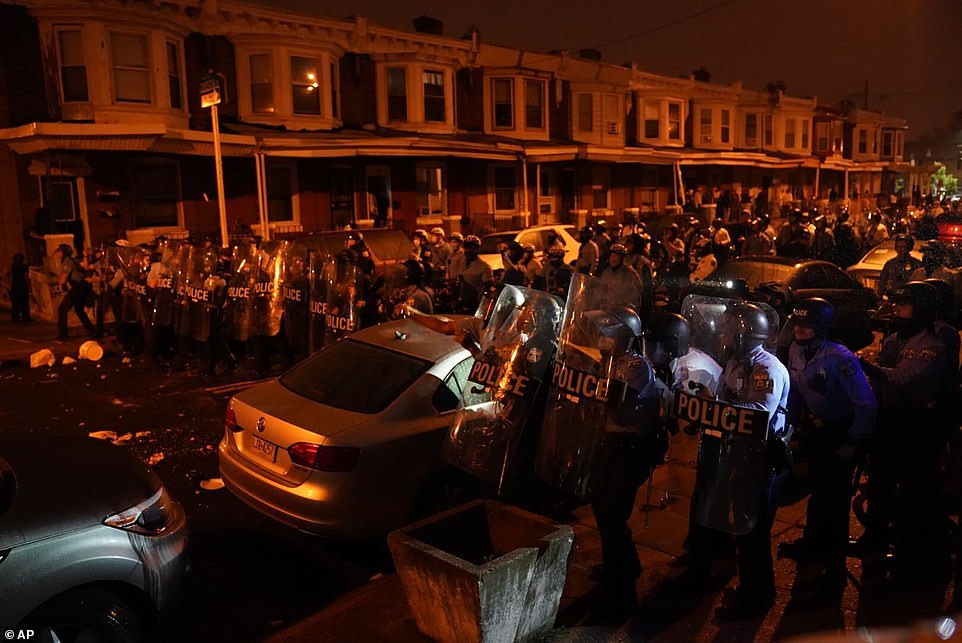 Protesters confronted police who stood in a line with riot shields behind metal barricades close to the police headquarters