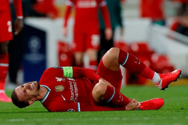 Jordan Henderson clutches his ankle after a hefty challenge in the first half