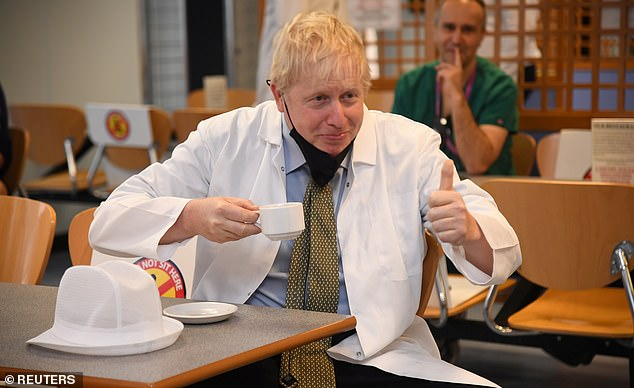 The 22-year-old Manchester United player has succeeded in making Boris Johnson and his party appear utterly indifferent to the plight of needy children this Christmas. (Above, the PM in a cafeteria at the Royal Berkshire Hospital in Reading yesterday)