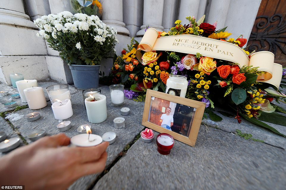 A woman puts a candle near a picture of Vincent Loques, sexton of Notre Dame church, one of the victims of a terror attack