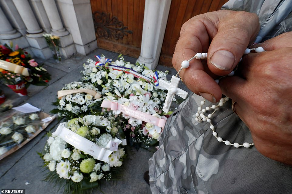 A man prays next candles and flowers left in memory of the victims of a knife attack in front of the Notre Dame church in Nice