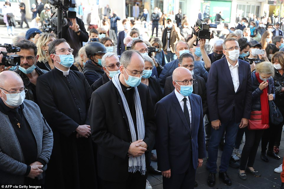 Notre-Dame de l'Assomption Basilica's Priest Franklin Parmentier (third left) and right-wing party Les Republicains MP Eric Ciotti (third right) pay homage at the church