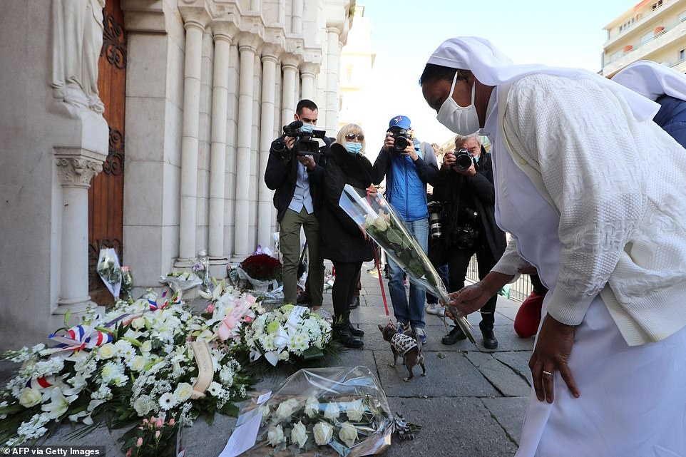 A nun lays flowers outside the Notre-Dame de l'Assomption Basilica in Nice