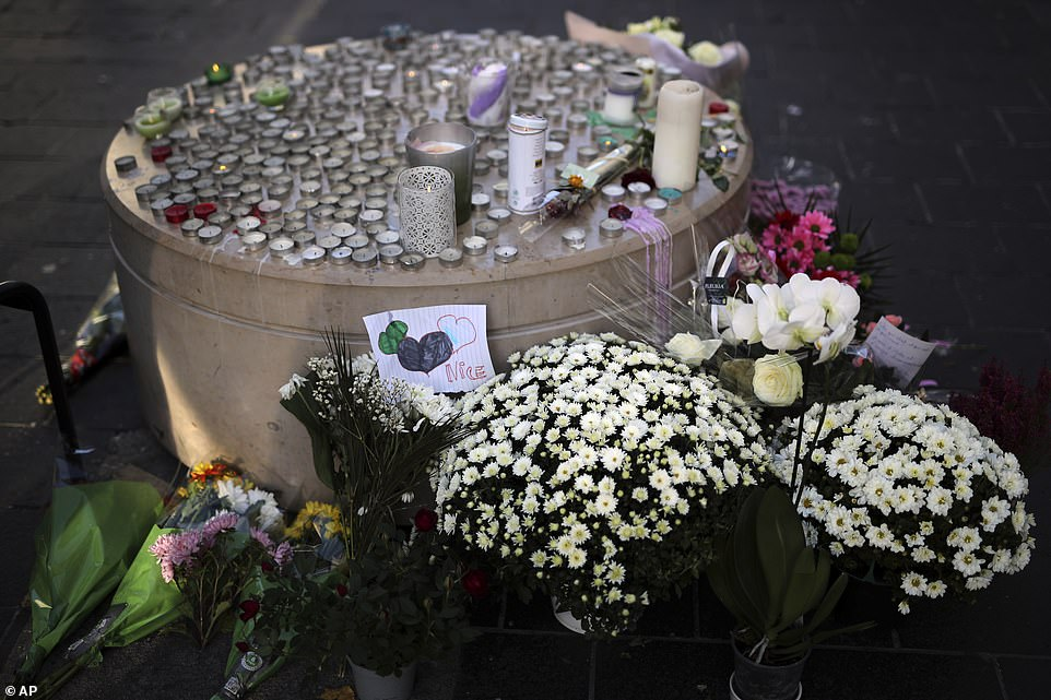 Flowers, messages and candles lie in front of the Notre Dame church, in Nice