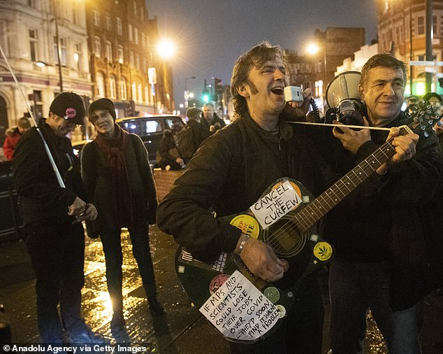 One of the protesters had a sign taped on his guitar reading: 'If MPs and scientist could lose their jobs over Covid, they'd soon find it wasn't a problem'