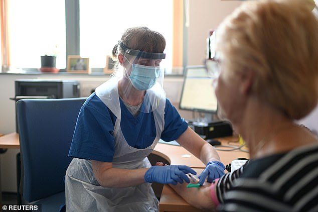 Many PPE contracts were awarded without the usual legal requirements for competitive tendering (Pictured: A nurse at a clinic in Grimsby wears PPE while taking blood from a patient)
