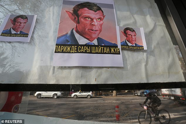 "Placards reading ""The yellow Devil is in Paris"" hang in a window as a mark of a protest against the publications of a cartoon of Prophet Mohammad in France and French President Emmanuel Macron's comments, in Almaty, Kazakhstan today"