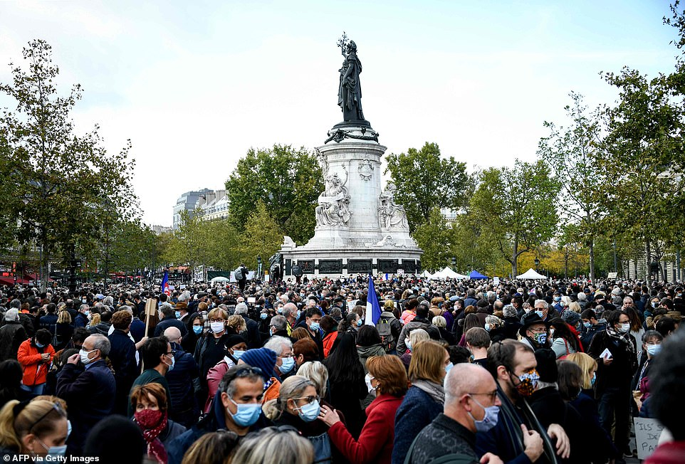 A crowd of people gather at the Place de la Republique in Paris on Sunday to pay tribute to murdered teacher Samuel Paty