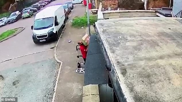 DPD driver takes a photo to show a parcel has been delivered before launching it over a 6ft wall