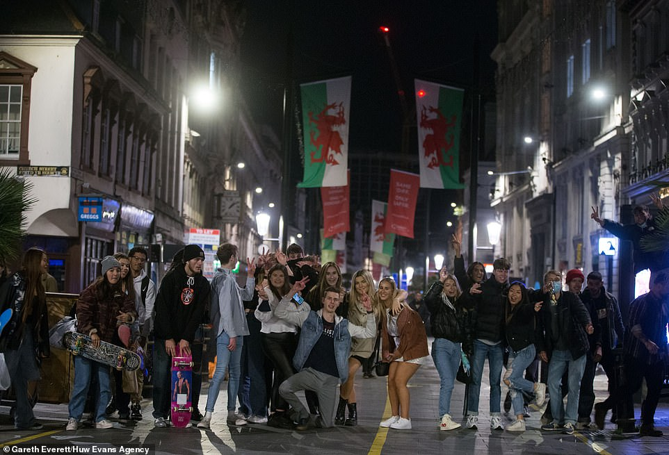 Maskless Welsh revellers pile on to the streets for the final time before national shutdown
