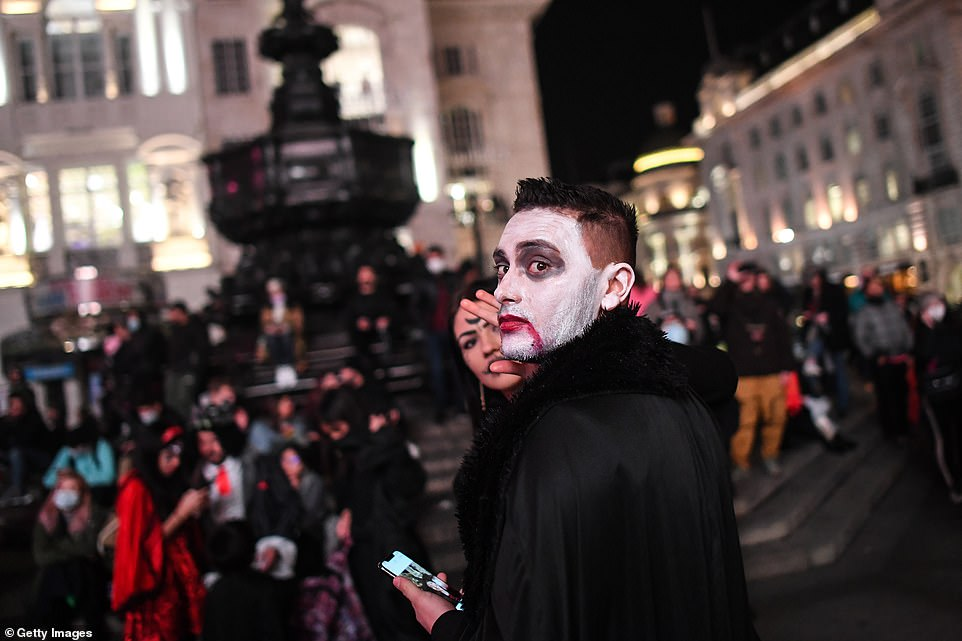 People in fancy dress are seen celebrating Halloween in Piccadilly Circus, London ahead of England's new shutdown