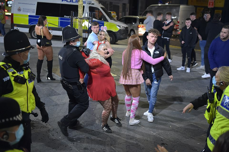 Police arrest a reveller as she and her friends party in the streets after the 10pm curfew in Newcastle city centre