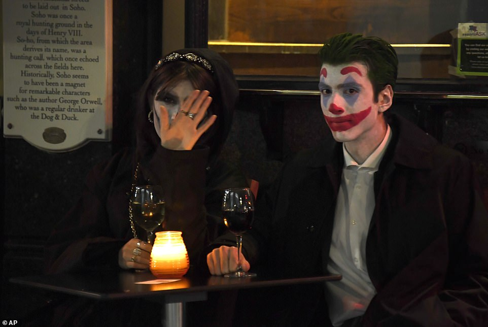 Revellers dressed up for Halloweenhave a drink outside a pub in Frith Street in Soho ahead of England's shutdown