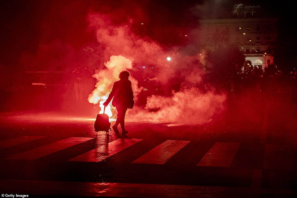 The clashes in Italy came as the country reported 31,758 new cases of the virus, a new daily record. The number of new fatalities stood at 297, nearly 100 more than the figure announced on Friday. Pictured: A woman passes by as protesters clash with police in Rome on Saturday