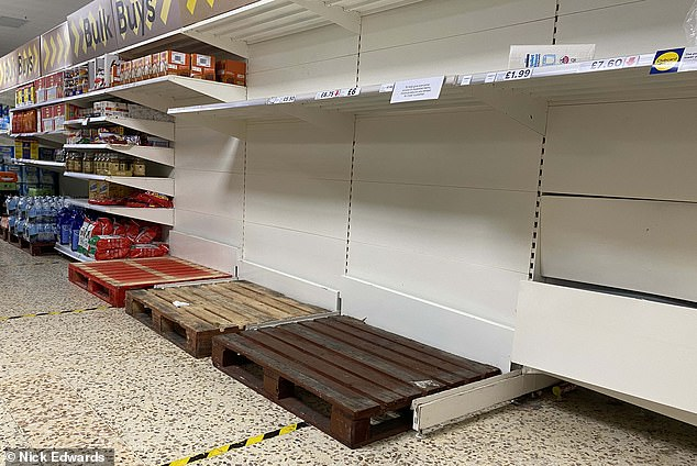 Customers empty the toilet paper shelves as a Tesco store in Surrey Queues following the Prime Minister's announcement