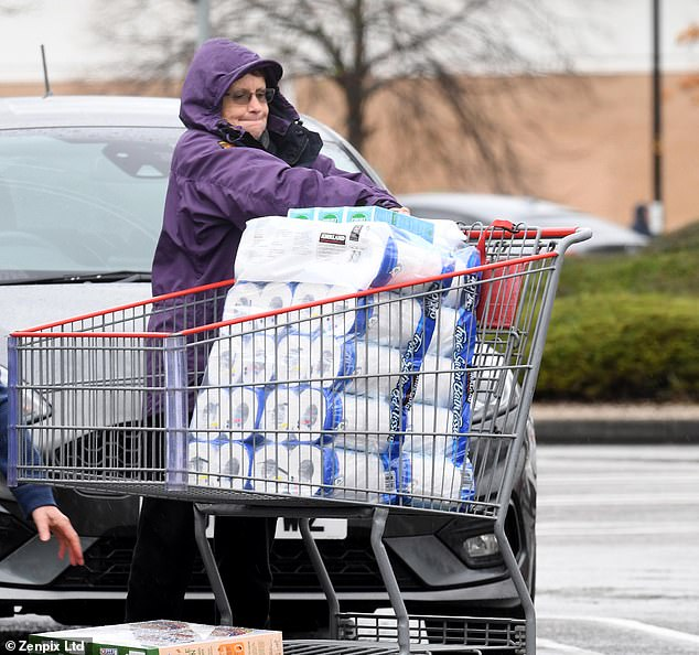 A woman piled rolls of toilet roll into her trolley before heading home from Costco in Manchester earlier today