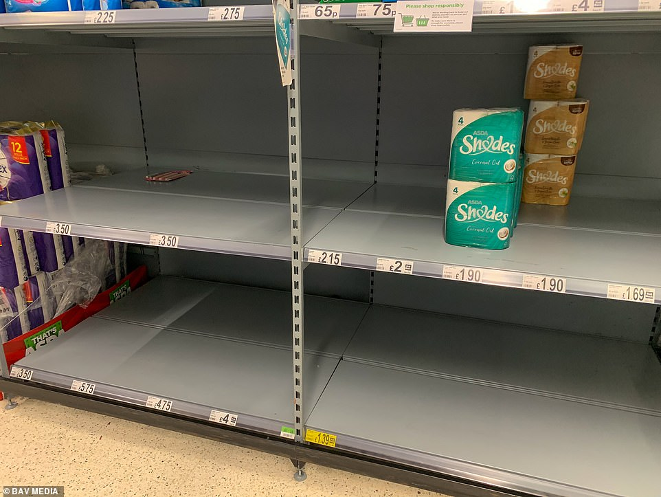Empty toilet paper shelves in Asda in Cambridge on Monday afternoon after shoppers picked them clean of supplies