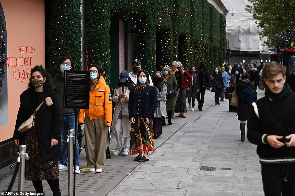 Shoppers queue outside Selfridges on Oxford Street in central London today ahead of the national lockdown on Thursday