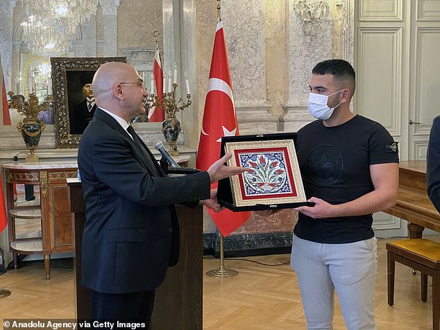 Mr Gultekin (pictured with Turkey's ambassador in Vienna) even ended up being shot in the calf by the terrorist as he was caught in gunfire while carrying out the rescue mission