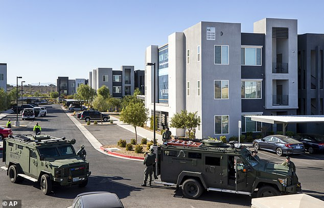 Cops received a 911 call about gunfire and 'someone with a possible gunshot wound in a nearby doorway'. When police arrived they found two people suffering from gunshot wounds and a 'possible suspect' sitting in a nearby car. When officers approached the suspect, it resulted in the shooting. SWAT vehicles pictured at the shooting scene