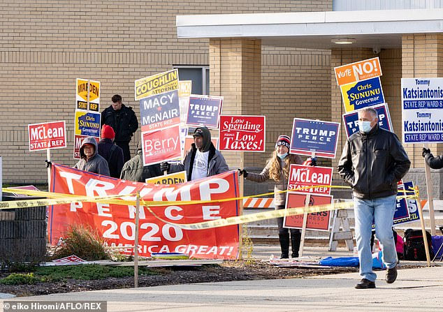 Manchester, New Hampshire: Trump supporters hold signs outside of a polling location as a voter walk out at Memorial High School election day