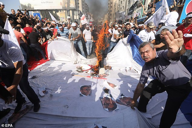 Palestinians in the West Bank stage a protest against French President Emmanuel Macron over his comments in defence of depictions of the Prophet Mohammed. The men are seen stamping on pictures of Macron's face and burning a French flat on October 30