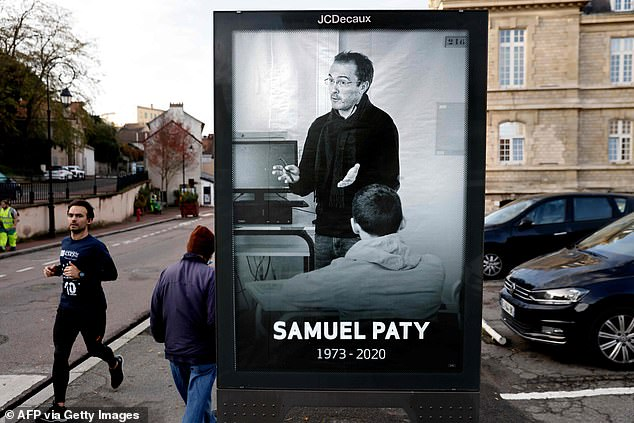 A poster of slain high school teacher Samuel Paty is displayed in Conflans-Sainte-Honorine, the Parisian suburb where he was killed on October 16