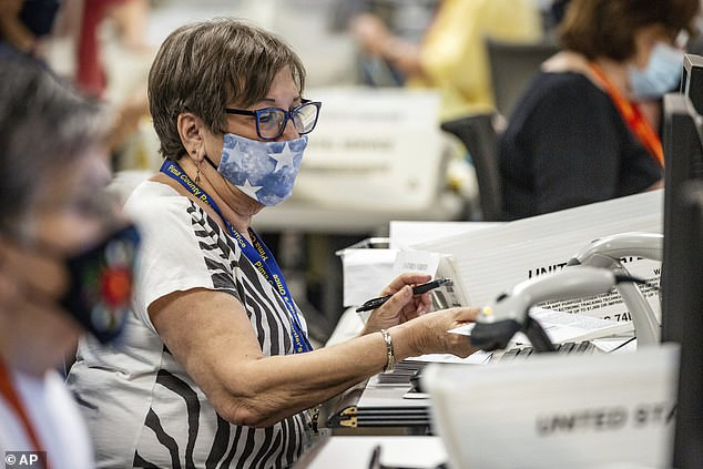 Pictured, an election worker scans a ballot while processing votes in Arizona.The uncertainty regarding the outcome of the presidential election in Arizona continued into Wednesday night as it was revealed that there are still 515,000 votes to be counted in the state