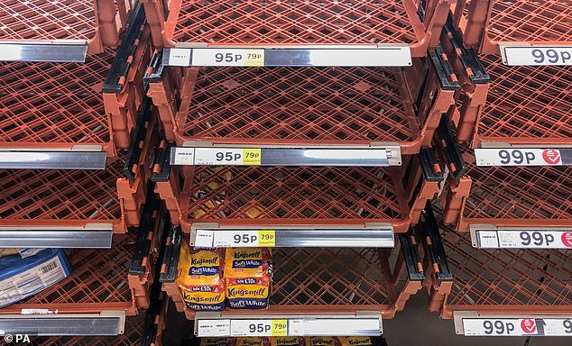 Bare shelves at a Tesco superstore in Cambridge ahead of the national lockdown, as customers stock up on loafs of bread
