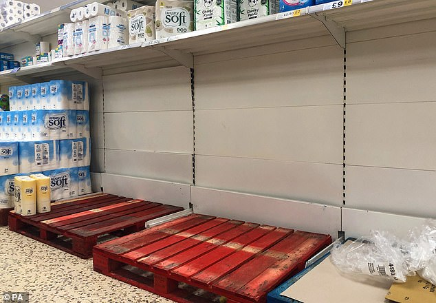 Shelves of toilet rolls are left bare after customers panic buy, despite the fact that food stores will remain open