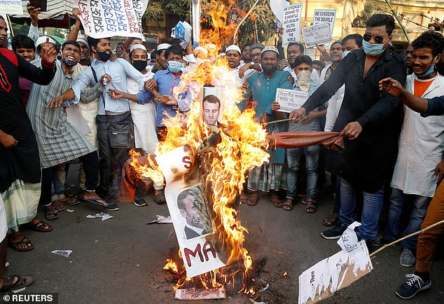 Protesters burn an effigy depicting French President Emmanuel Macron during a demonstration in Kolkata, India, on November 4