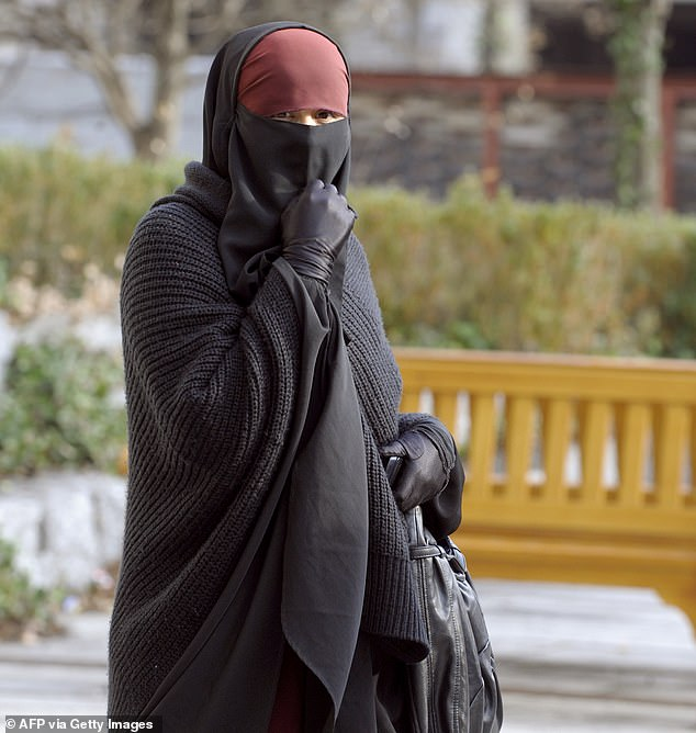 The President said 'small girls wear full veil and are raised to hate our values' in some areas of France. Pictured: A woman wearing a niqab, the islamic full veil, walks in a street of Lyon, eastern France