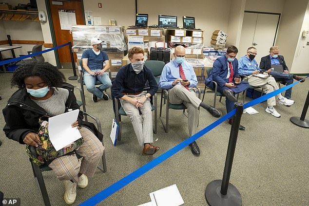 President Trump complained his campaign was not allowed to have observers watch ballot counting but, above, members of both theDemocratic and Republican Party watch as Lehigh County workers count ballots in Allentown, Pa.