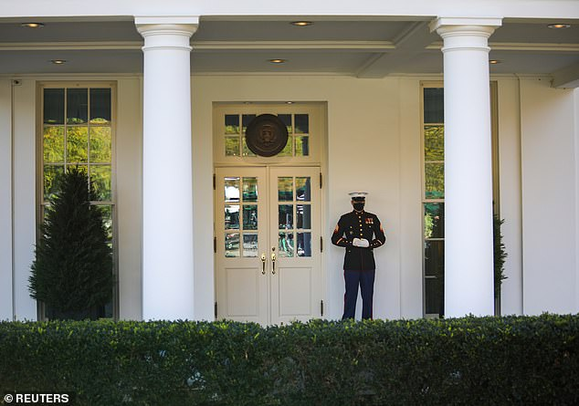 A United States Marine stands guard in front of the west wing at the White House, signalling that President Trump has entered