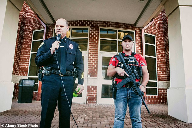 Newport News Police Chief Drew addresses rally attendees with Boogaloo Boi and rally organizer Dunn during an open carry rally in front of his headquarters