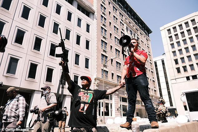 Protest organizer Mike Dunn and a protester with a gun raised in the air pose for photos during an open carry protest on July 4 in Richmond, Virginia. People attended an event in Virginia tagged Stand with Virginia, Support the 2nd amendment