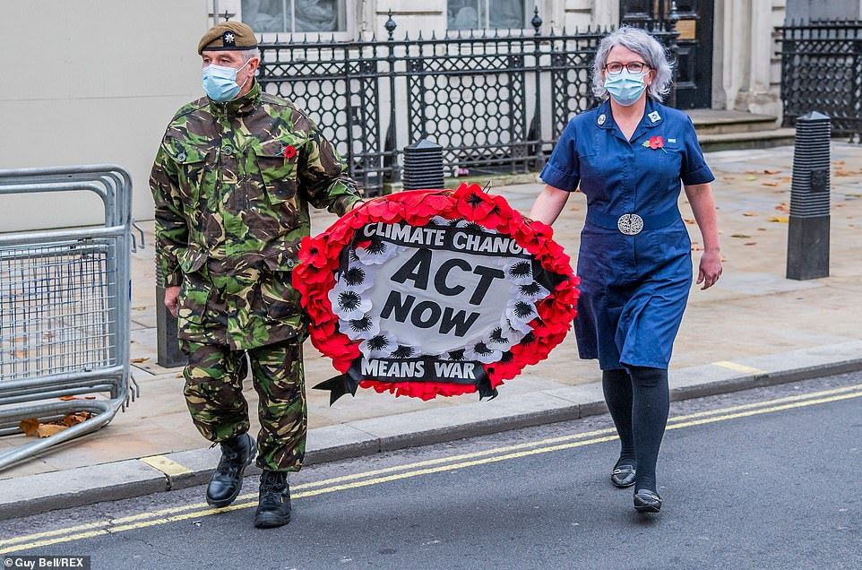 Eco-warriors unveiled a banner reading 'Honour Their Sacrifice, Climate Change Means War' at the memorial on Whitehall, central London, at 8am