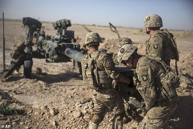 U.S. Soldiers with Task Force Iron maneuver an M-777 howitzer, so it can be towed into position at Bost Airfield, Afghanistan