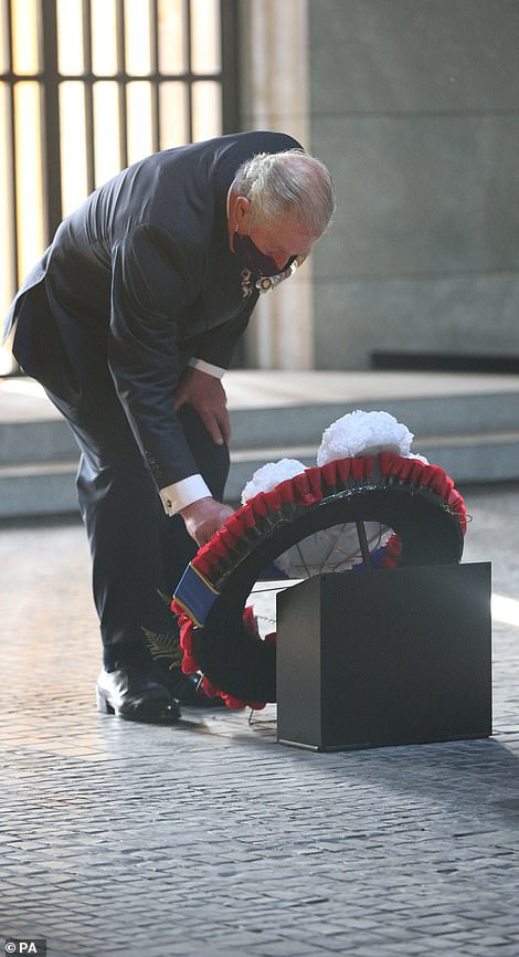 Prince Charles is pictured paying his respects as he stands and then kneels in the Neue Wache in front of a wreath of flowers laid on behalf of Britain's Royal Family