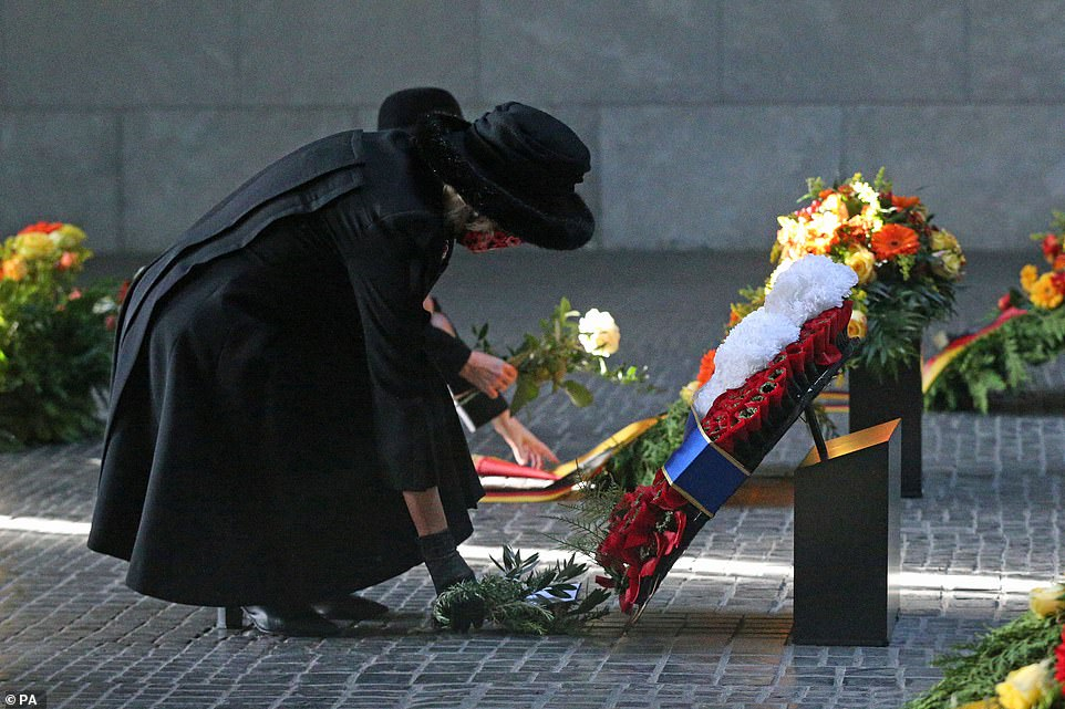 The Duchess of Cornwall lays a posy of flowers by The Prince of Wales' Wreathe of Remembrance at the Neue Wache Central Memorial