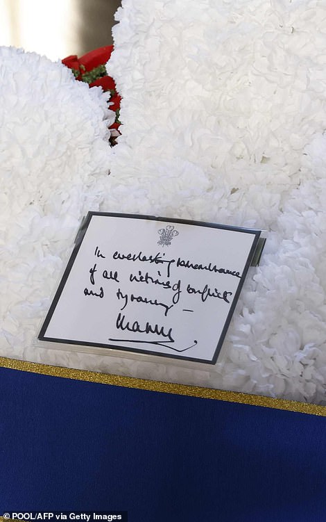 A wreath of flowers laid by Britain's Royals is pictured prior a ceremony on the national Memorial Day at the Neue Wache in Berlin. The note reads: 'In everlasting remembrance of all victims of conflict and tyranny - Charles'