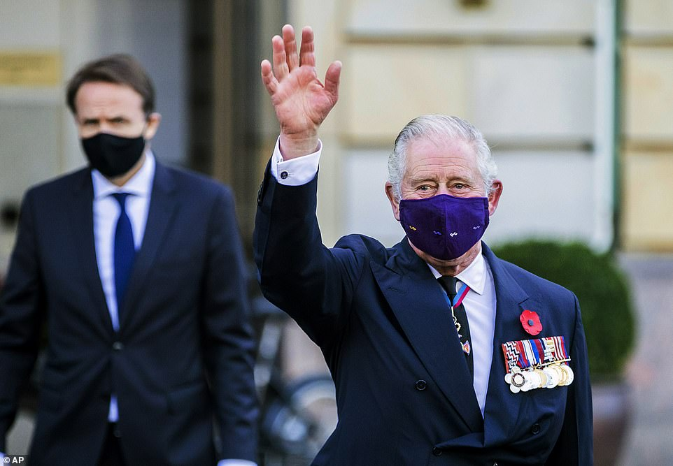Wearing a purple velvet protective face covering, the Prince of Wales waves to onlookers as he leaves the Hotel Adlon in Berlin for the ceremony