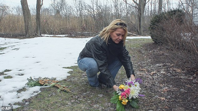 Pictured: Barbara Beach Hamburg's sister, Conway Beach, leaves a flower bouquet outside the Madison, Connecticut, home where she was killed