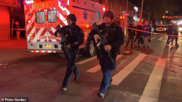 Heavily armed police in tactical gear are seen above in Richmond Hill, Queens, on Tuesday night