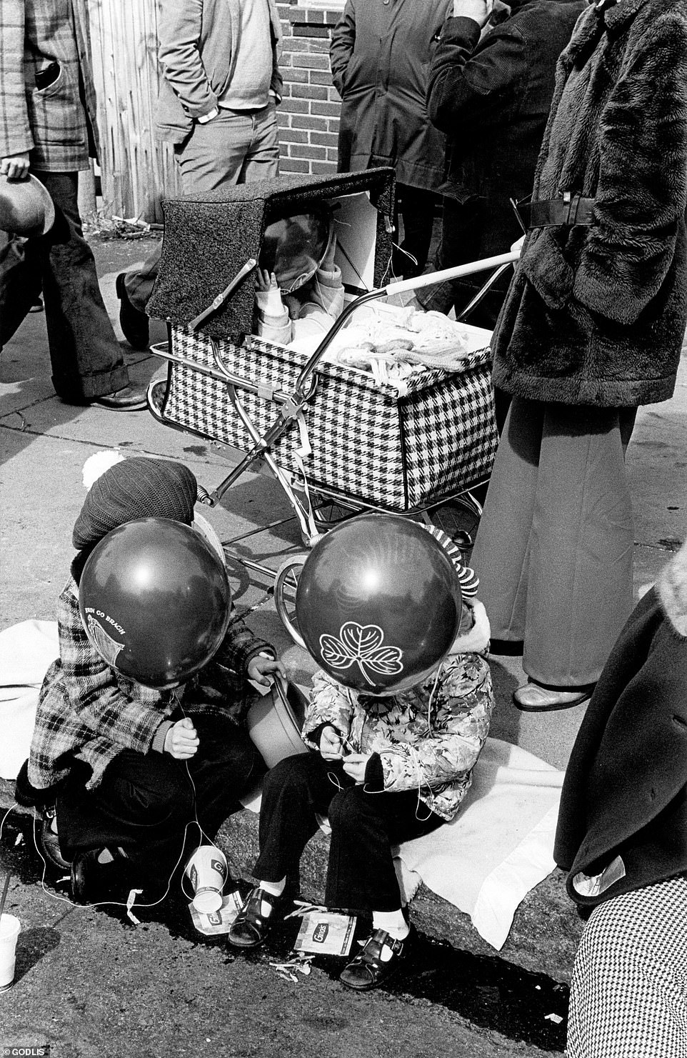 Balloons obscure the faces of two children sitting on a busy curb in Manhattan. Godlis said: 'Walking around and catching the rhythm of the street while taking photographs is like therapy to me. It grounds me'