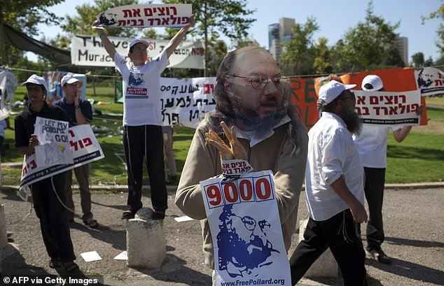 An Israeli youth demonstrator holds a picture and an effigy of Pollard during a protest calling for his release in front of the American consulate in Jerusalem in 2011