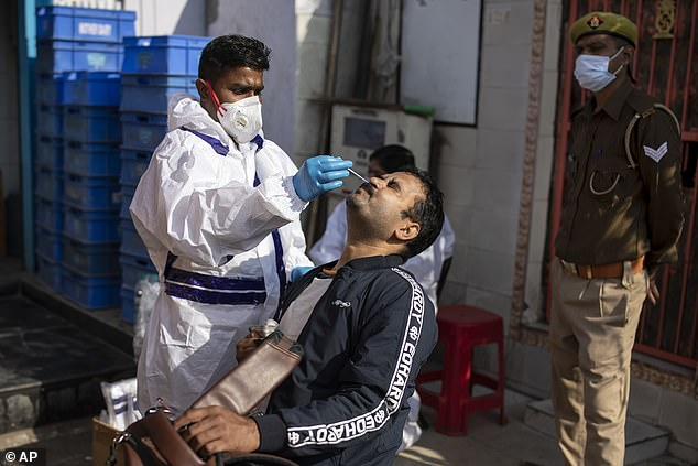 A health worker takes a nasal swab in New Delhi as India passed a total of 9million infections