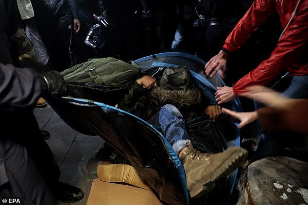 Police officers attempt to physically remove a migrant from his tent in Place de la République on Monday night