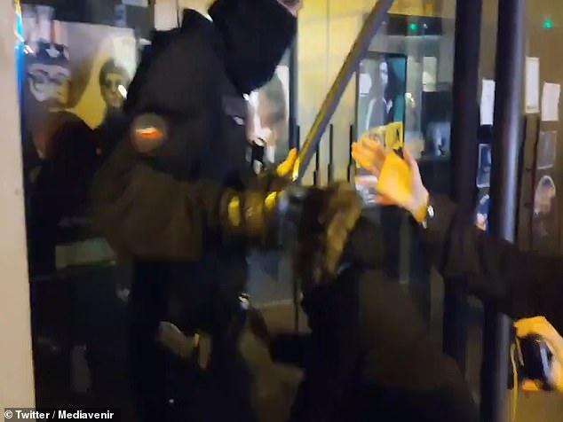 A person tries to intervene as police officers appear to beat French journalist Rémy Buisine moments after he posted a video of them tipping a refugee out of his tent